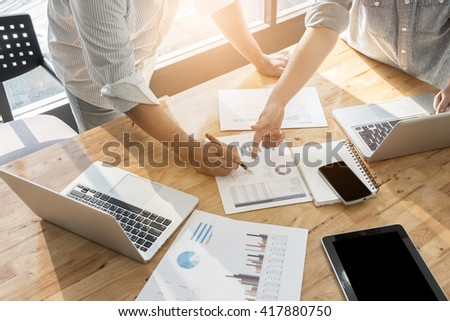 Close-up of female and male hands pointing at turnover graph while discussing it - stock photo