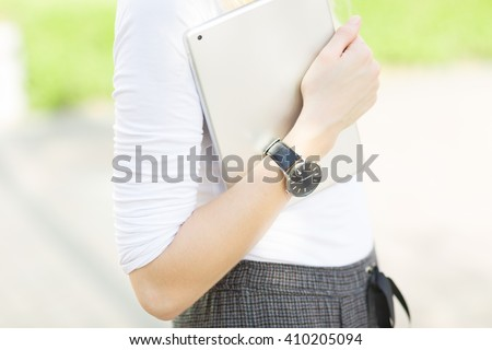 Close-up of female arm wearing a watch and carrying a digital tablet outdoors. - stock photo