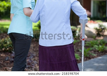 Close-up of female caregiver helping woman with a crutch  - stock photo