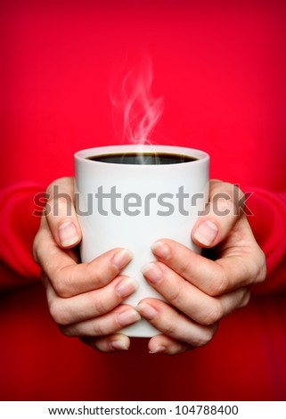 Close up of female caucasian hands holding white mug with hot coffee - stock photo