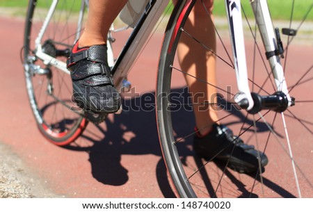 Close-up of female cyclist standing with her road racing bike. Shallow D.O.F.