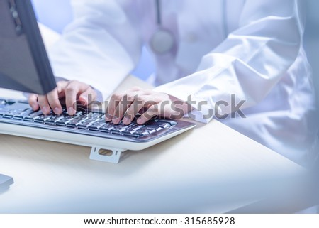 Close-up Of Female Doctor Filling The Medical Form - stock photo