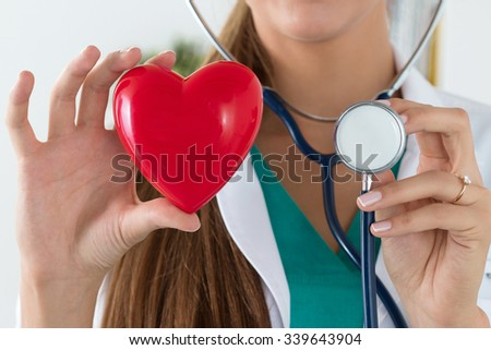 Close-up of female doctor hands holding read heart and stethoscope head. Healthcare and medical concept - stock photo