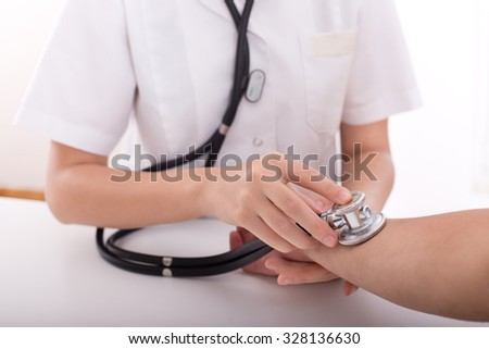Close up of female doctor hands measuring male patient's pulse with stethoscope