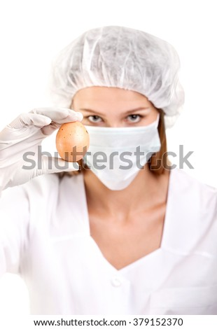 Close-up of Female Doctor or Scientist with Egg on a White Background - stock photo