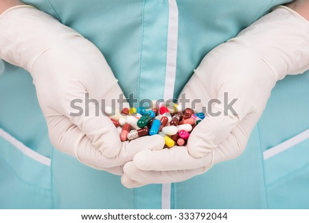 Close-up of female doctor's hand holding pills for his patient