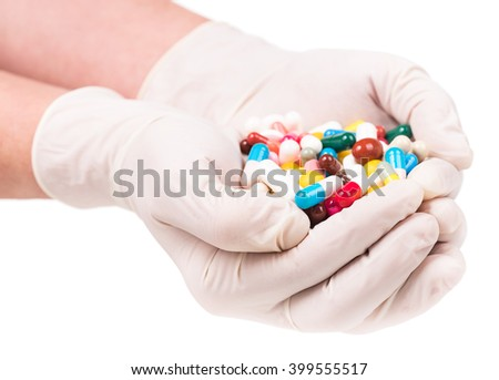 Close-up of female doctor's hands holding pills isolated over white background