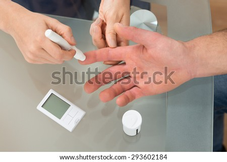 Close-up Of Female Doctor Using Lancelet On Man At Desk In Clinic - stock photo