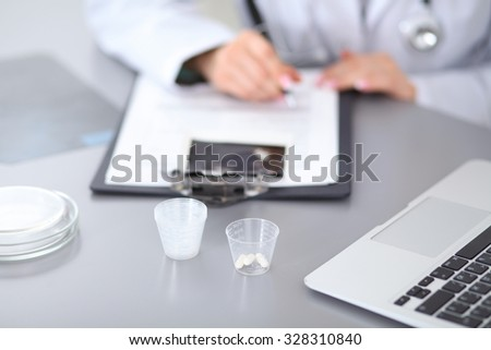 Close up of female doctor  writing a medical prescription, sitting at the table in hospital - stock photo