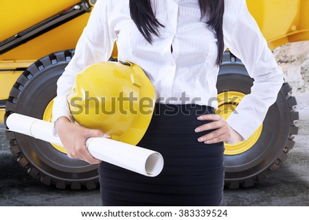 Close up of female engineer standing near the dump truck while holding helmet and blueprint - stock photo