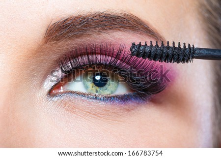 Close up of female eye with bright make-up and brush applying mascara on eyelashes - stock photo