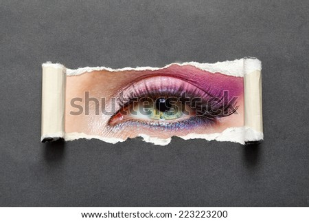 Close up of female eye with pink make-up on torn paper. Concept of fashion and beauty.