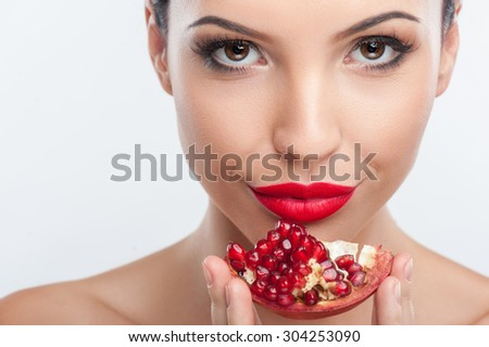 Close up of female face. The beautiful girl is touching a pomegranate to her chin. Her lips are red. She is smiling and looking at the camera with joy. Isolated - stock photo
