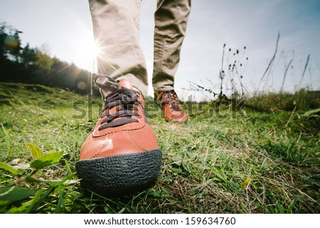 Close-up of female feet in sneakers running outdoors - stock photo