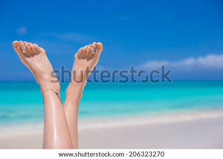 Close up of female feet on white sandy beach