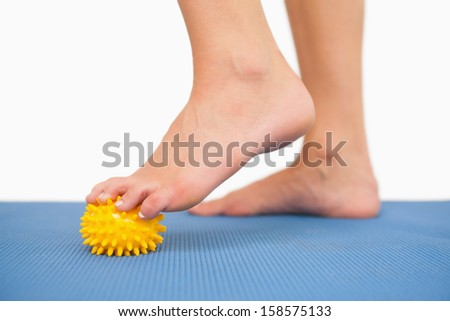 Close up of female feet touching yellow massage ball on blue floor