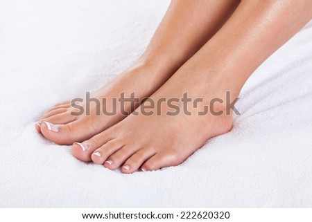 Close-up of female feet with french pedicure - stock photo