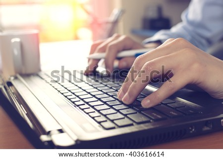 Close up of female fingers on the keyboard,back lit