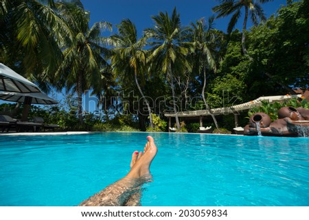 Close-up of female foot in the blue water on the tropical pool. Vacation holidays. - stock photo
