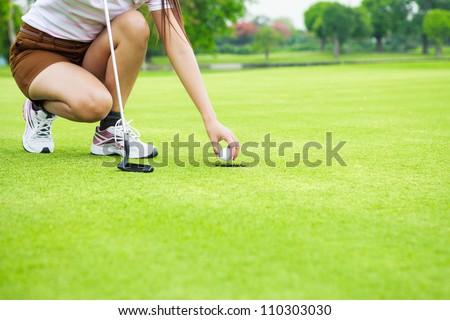 Close up of female golf player picking up ball from hole at green - stock photo