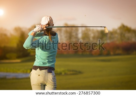 Close up of female golf player swinging golf club on fairway during sunset. - stock photo