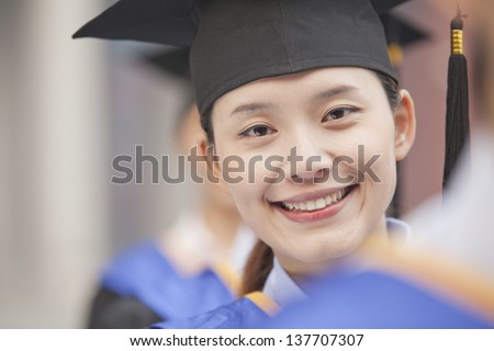 Close Up of Female Graduate Student Standing in a Row of Graduates