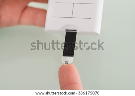 Close-up Of Female Hand Checking Blood Sugar Level With Glucometer - stock photo