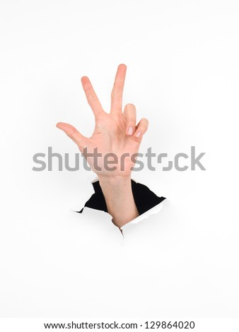 close-up of female hand coming out from a hole in a paper, counting number three gesture, isolated on white - stock photo