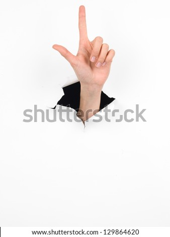close-up of female hand coming out from a hole in a paper, counting number two gesture, isolated on white