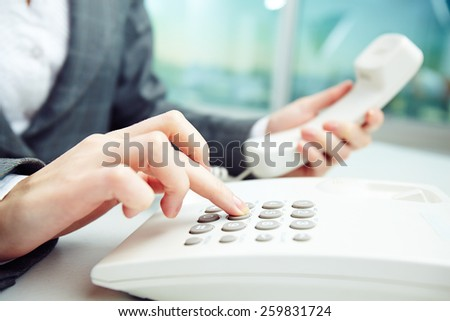 Close-up of female hand dialing number - stock photo