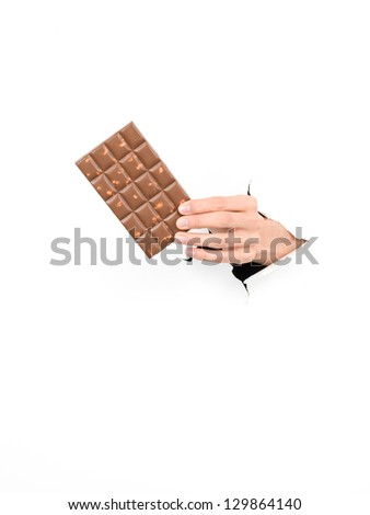 close-up of female hand holding a bar of chocolate throught a white paper, isolated - stock photo