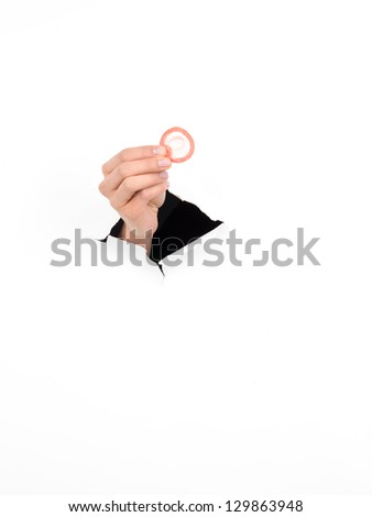 close-up of female hand holding a condom through a torn white paper, isolated - stock photo