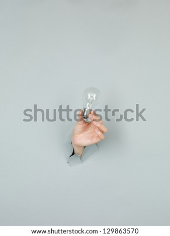 close-up of female hand holding a lightbulb through a torn grey paper