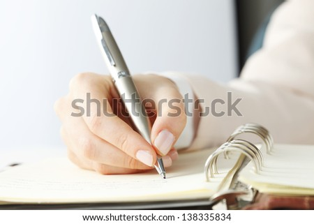 Close-up of female hand holding a pen and writing some research notes in the appointment book  - stock photo