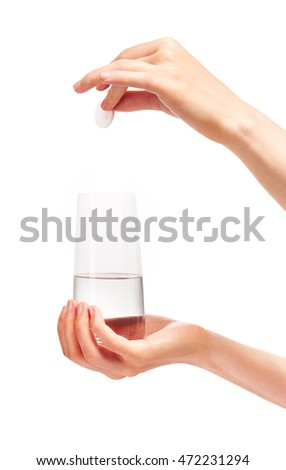 Close up of female hand holding large white round effervescent tablet over clean transparent drinking glass with water against white background. Clipping path for glass border included.