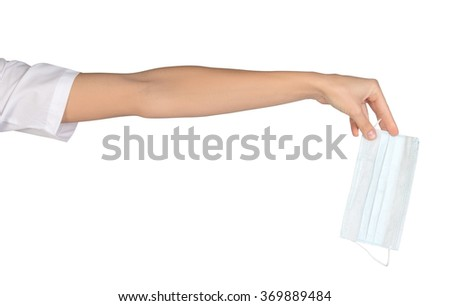 Close-up of female hand holding surgical mask - stock photo
