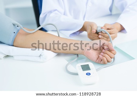 Close-up of female hand in blood pressure gauge - stock photo
