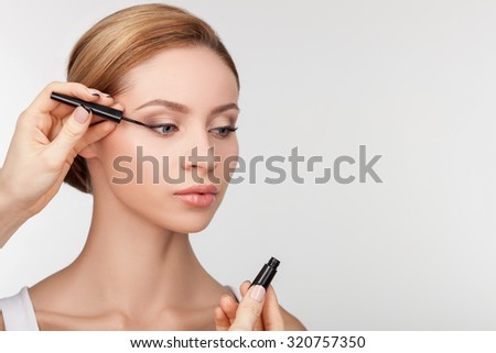 Close up of female hand of make-up artist is painting eyes of model. The worker is holding eyeliner. The pretty girl is standing and looking forward confidently. Isolated and copy space in right side - stock photo