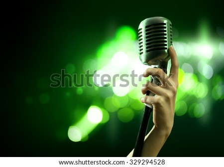 Close up of female hand on blurred background holding microphone