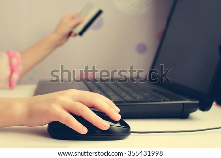 Close up of female hand on computer mouse and holding a credit  card. The concept of online shopping. - stock photo