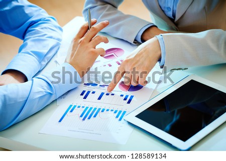Close-up of female hand pointing at business document while explaining chart - stock photo