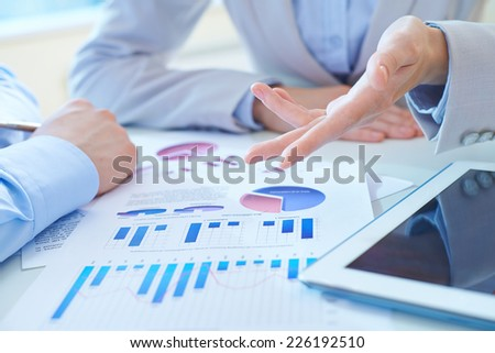 Close-up of female hand pointing at financial analysis while explaining it - stock photo