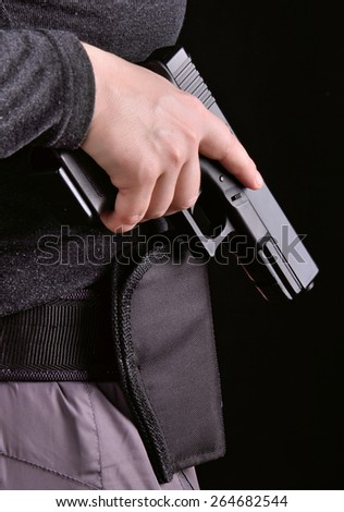 Close up of female hand pulled gun from the holster on a black background - stock photo