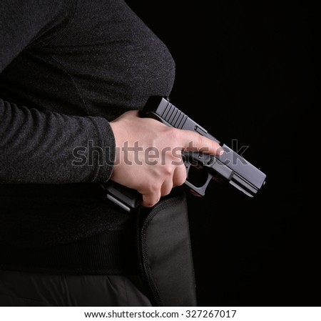 Close up of female hand pulled gun from the holster on a white background
