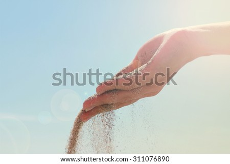 Close-up of female hand releasing dropping sand. Sand flowing through the hands against blue sky. Summer beach holiday vacation concept - stock photo