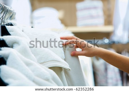 Close up of female hand touching a white jacket in the shop - stock photo