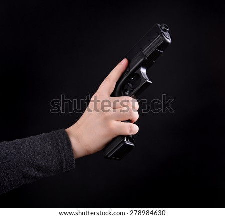 Close up of female hand with gun on a black background - stock photo