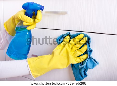 Close up of female hand with rubber gloves and detergent in sprayer cleaning drawers - stock photo