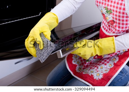 Close up of female hand with yellow protective gloves cleaning oven - stock photo