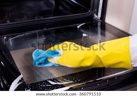 Close up of female hand with yellow protective gloves cleaning oven door - stock photo